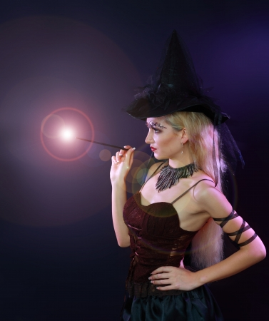 Fantasy magic portrait of sexy beautiful woman making spell with magic wand photo