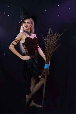 Sexy beautiful witch with broom on dark background Stock Photo - 17067623