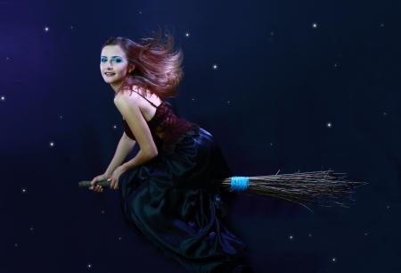 Sexy brunette witch flying on broom on a dark sky with stars photo