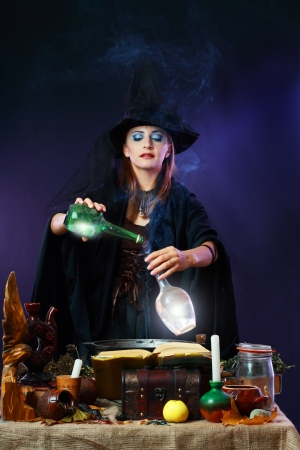 Sexy witch on a dark background making potion on wizard kitchen Stock Photo - 17067991