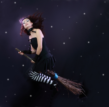Sexy brunette witch flying on broom on a dark sky with stars Stock Photo - 17067704
