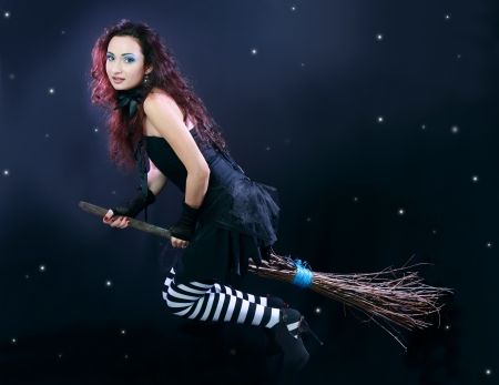 Sexy brunette witch flying on broom on a dark sky with stars Stock Photo - 17067490
