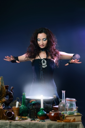 Sexy witch on a dark background making potion on wizard kitchen photo