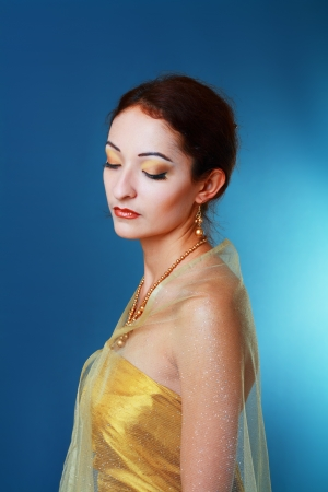 beautiful asian woman in golden dress studio shot photo