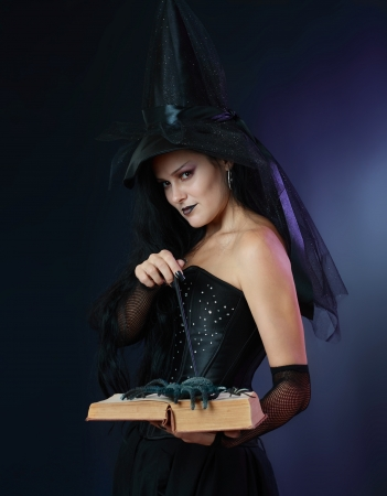 Charming halloween witch with magic wand and book over black and blue background photo