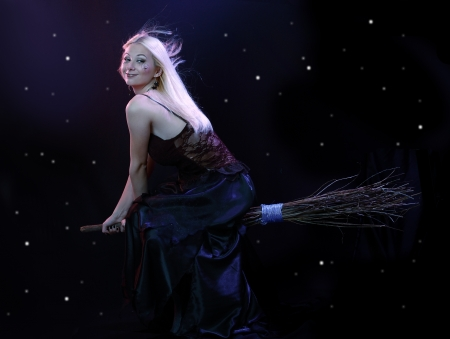 Sexy blond witch flying on broom on a dark sky with stars Stock Photo - 17067417