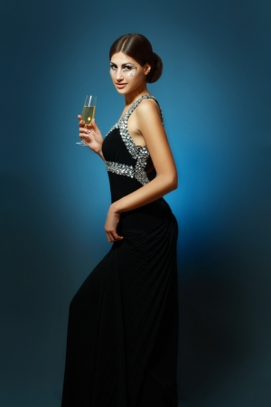 beautiful young woman with creative face art make up drinking Champagne photo