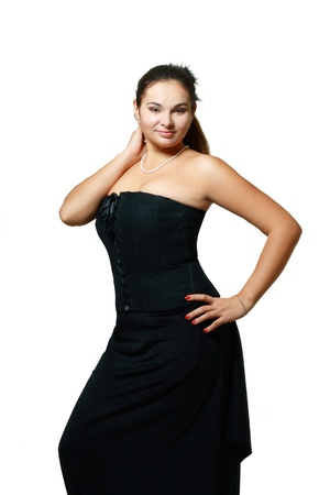 portrait of beautiful plus size young blond woman posing on white in black dress  photo