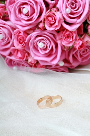 conept: Pair of golden wedding rings with pearl and flowers. invitation card conept