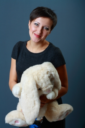 grown up: grown up woman with beloved toy in her hands over dark background Stock Photo