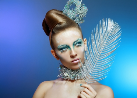 Ice-queen. Young woman in creative image with silver blue artistic make-up and perfect hairstyle. photo