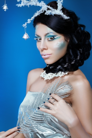 snow-queen. Young woman in creative image with silver blue artistic make-up and perfect hairstyle. photo