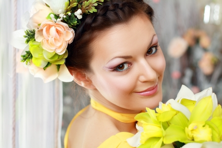 Beautiful girl with stylish makeup and flowers around her. photo
