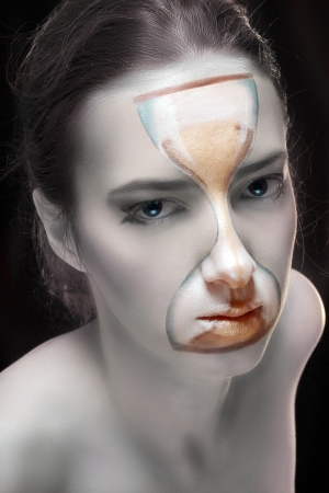 the hourglass, sand watches, face art painting on the face of young woman Stock Photo - 17383299