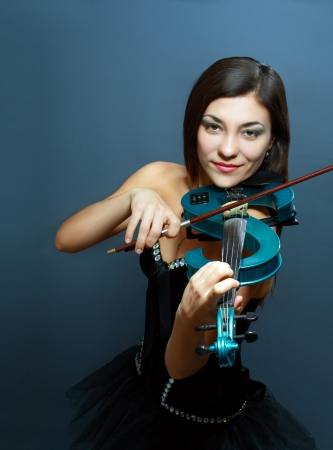 beautiful girl with blue electric violin on dark blue background photo