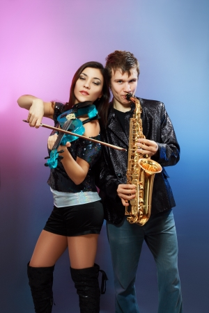 Couple of professional musicians in modern style posing in costumes at studio photo