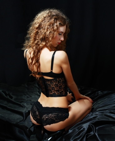 hot beautiful young woman in black lingerie over dark background photo