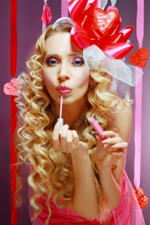 beautiful stylish valentine woman applying lip gloss on her lips dressing up for party photo