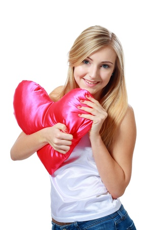 Sweet smiling young blond woman holding red heart shape pillow  photo