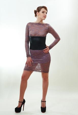 Fashionable young woman in beautiful dress posing at studio. photo