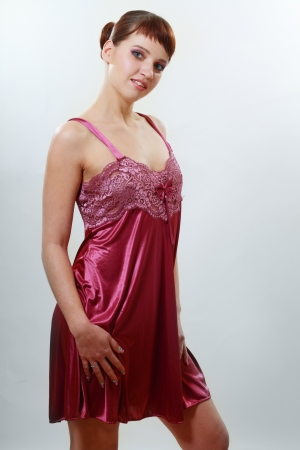nightgown: A woman wears a beautiful red satin sleepwear