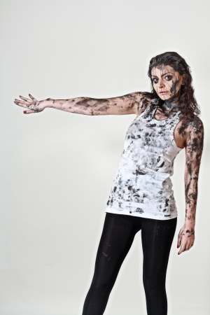 scary crazy woman with face and body covered in mud photo