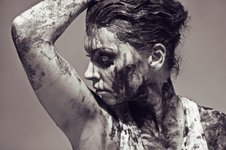 a close up of a womans face and hands covered in mud photo