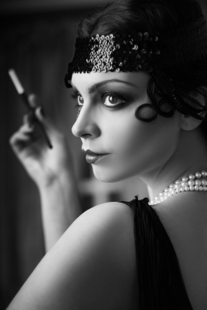 Beautiful young woman close up portrait in retro flapper style headband bw Vogue style vintage photo