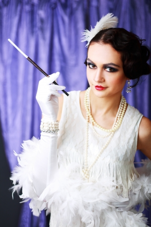 Beautiful young woman portrait in retro flapper style headband Vogue style vintage and with cigarette holder in her hand photo