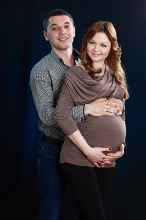 enceinte: beautiful pregnant woman and man in the studio over dark background