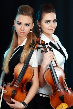 two beautiful young woman with violins over dark background Stock Photo - 19249690