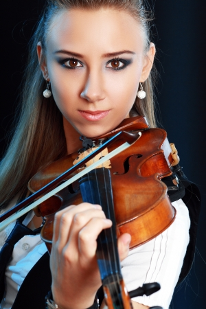 Violinist girl playing on violin over dark background Stock Photo - 19249688