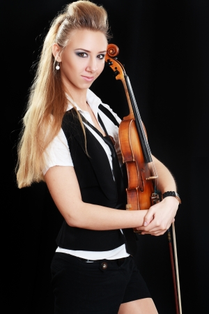 Violinist girl hold violin over dark background looking at camera Stock Photo - 19249624