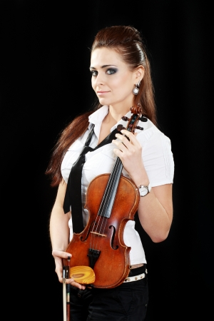 Violinist girl hold violin over dark background looking at camera Stock Photo - 19249615