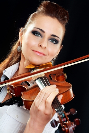 Violinist girl playing on violin over dark background Stock Photo - 19249663