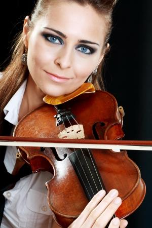 Violinist girl playing on violin over dark background photo