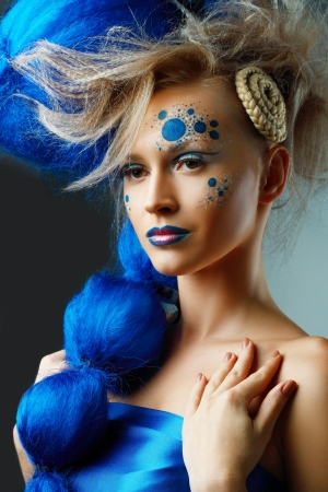 beautiful fashionable young woman with creative fantasy hairstyle with blue hairs and art make up  photo