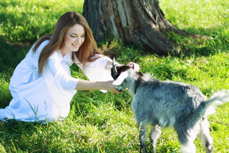 Portrait of a young woman playing a baby goat outdoor photo