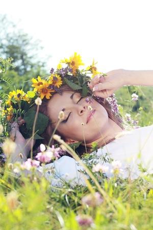 schöne junge Frau auf der Wiese mit weißen Blüten an einem warmen Sommertag Standard-Bild