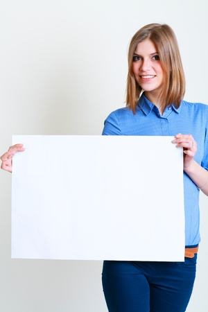 A beautiful woman holds out a big blank card Isolated on white background photo