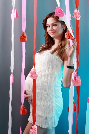 beautiful pregnant woman in dress over blue background photo