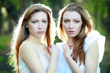 two Beautiful woman twins in the morning park photo
