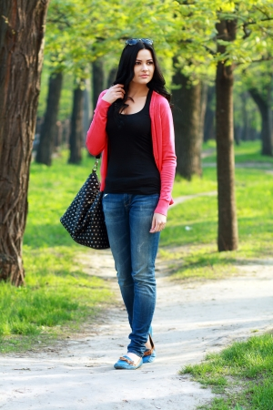 beautiful university student walking on outside campus, green park photo