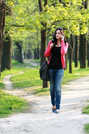 Mooie brunette vrouw belt op de telefoon lopen buiten in het park