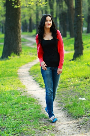 young woman walking on path in city park  photo