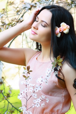 beautiful happy brunette woman in the park on a warm spring day with blossom flowers around her photo