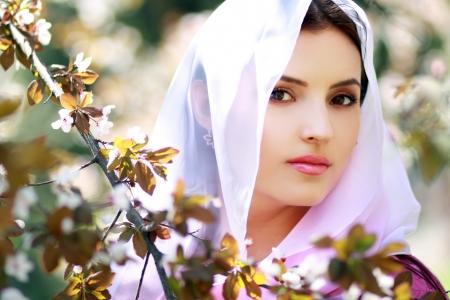 Jonge rustige vrouw buitenshuis portret. Lentebloesem