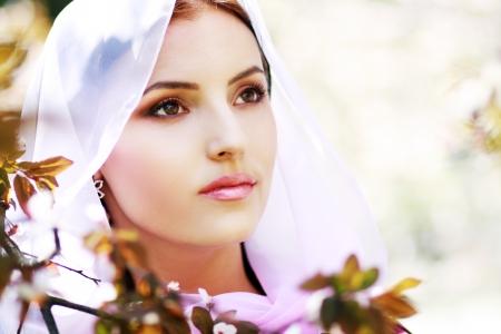 femme musulmane: Jeune femme tranquille en plein air portrait. Spring blossom