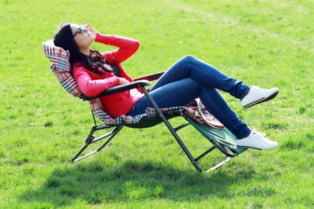 beautiful brunette woman relaxing on lounger in the spring grass photo