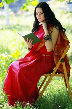 A shot of an asian or indian student in traditional clothes studying on campus park photo